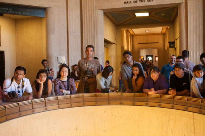 "A crowd of tourists are entranced by ""Foucault pendulum"" at the Griffith Observatory."